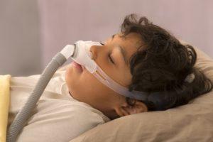 child resting with sleep apnea CPAP system