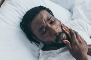 Man lying in bed suffering from TMJ pain