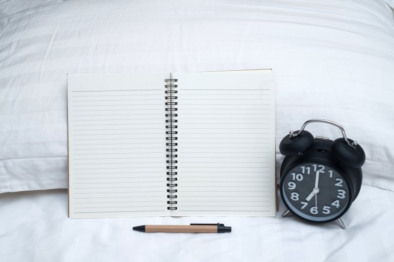 Open notebook on bed with pen and alarm clock