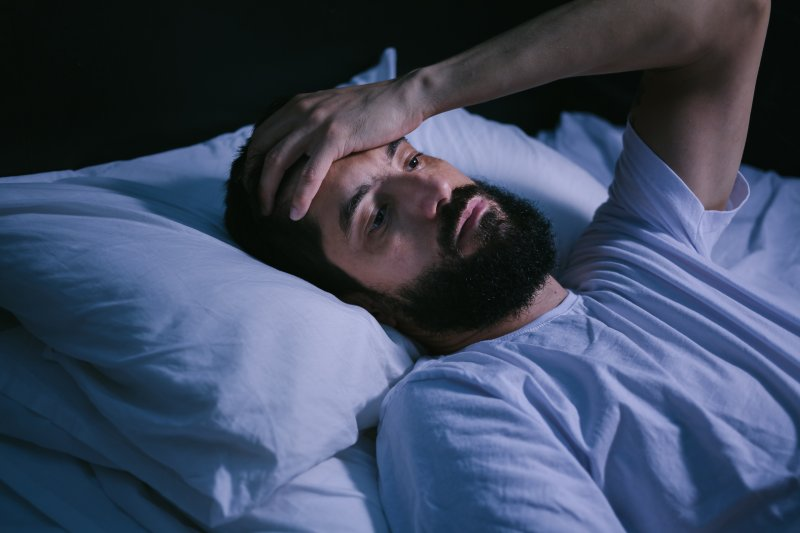 Bearded man being kept up by his sleep apnea